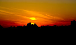 Evening city and beautiful burning sunset. Color photo of background of burning sunset behind a city Stock Photo