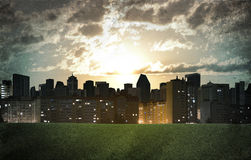 Evening city. Buildings and green grass field. Grunge style Royalty Free Stock Photo