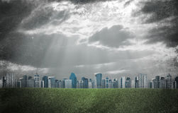 Evening city. Buildings and green grass field Royalty Free Stock Photo