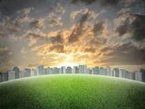 Evening city. Buildings and green grass field Stock Photography