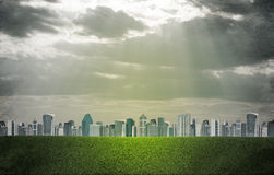 Evening city. Buildings and green grass field Royalty Free Stock Images