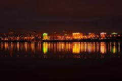 Evening city landscape with reflection in the ice lake Royalty Free Stock Photo