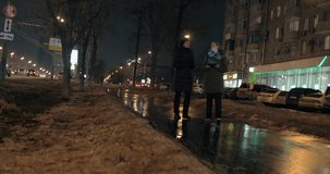 Night city with car traffic and women friends walking in the street. Evening city view with car traffic on the road and two women friends walking in the street stock video footage