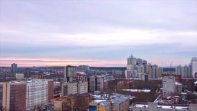 Evening city in winter timelapse. Evening city in winter view from roof timelapse. Panoramic view on the town and roofs Stock Photo