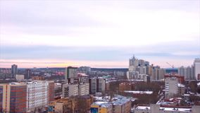 Evening city in winter timelapse. Evening city in winter view from roof timelapse. Panoramic view on the town and roofs Stock Photos