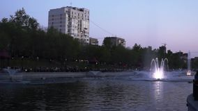 Evening cityscape with light and music fountain Ussuriysky in the lower city pond, KHABAROVSK, RUSSIA stock video footage
