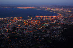 Evening cityscape of town from birdview. Evening cityscape of the town with ocean bay from bird view - lights on streets and in a port, cape town south africa Stock Photography