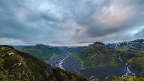 Evening clouds flying over Iceland mountains landscape. Time lapse. Colorful evening with gray clouds moving over sky in Iceland volcanic mountains and river stock footage