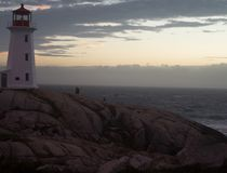 Evening clouds with sun shining through at Peggy`s Cove Lighthouse stock images