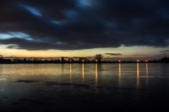 Evening clouds after sunset on a frozen lake and reflecting lights in the ice. Winter view stock photography