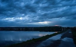 Evening cloudy sky over the lake. Night landscape after the rain.  stock photo