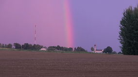 Evening Colored rainbow over field stock footage