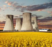 Evening colored view of nuclear power plant Dukovany. With golden glowering field of rapeseed - Czech Republic - two possibility for production of energy Stock Photos