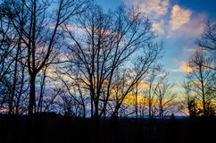 Evening Colors on Top of the Mountain. Trees silhouetted against a beautifully colored cloudy evening sky in the Blue Ridge Mountains in North Carolina stock photo