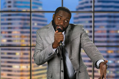 Evening comedy show on television. Black stand-up comedian. Evening comedy show on television. Comedian on urban background. Telling jokes on stage Royalty Free Stock Photography