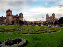 Evening in Cusco Plaza. The main plaza of Cusco, Peru as evening twilight descends on the city. Pedestrians walk around the square bordered by churches, a park Stock Image