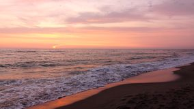 Evening dark sea in the background perfectly colorful sunset. Evening dark sea and sandy beach in the background perfectly white yellow pink purple colorful stock video