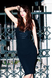Evening dress. Young woman in elegant tight evening dress outdoor shot in front of wrought iron gate Stock Photos