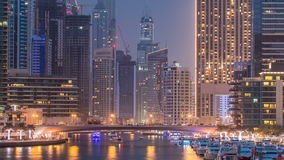 Evening Dubai marina city centre with floating vessels day to night timelapse. Marine boat interchange with view on Dubai marina illuminated city centre in stock video footage