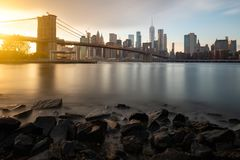 Evening by the East River in New York City. View of Brooklyn Bridge and Lower Manhattan during sunset royalty free stock photo