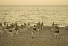 Evening empty beach with chairs and striped umbrellas. Resort landscape. Vintage retro filter stock photo