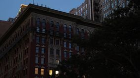 Evening Establishing Shot of Typical Red Brick Apartment Building. A nighttime establishing shot (NX) of a typical red brick apartment or office building in stock video