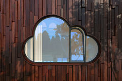 Evening facade of a modern building with window like a cloud. The window like a cloud icon on modern wood planks fasad. The rays of the evening sun through the Royalty Free Stock Images