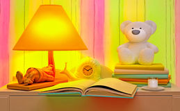 Evening fairy tale. Books and a toy bear, an alarm clock and a lamp are located on a table. Stock Photo