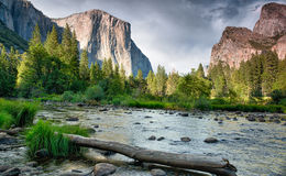 Evening falling in Yosemite. The evening skies are a dramatic backdrop to the water and mountians in the distance Royalty Free Stock Photography