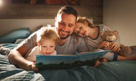 Evening family reading. father reads children . book before goin. Evening family reading. father reads children a book before going to bed royalty free stock photos