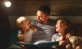 Evening family reading. father reads children . book before going to bed. Evening family reading. father reads children a book before going to bed stock images