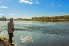 Evening fishing on the river. An elderly man on a fishing trip stands on the river bank in the evening Stock Image