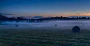 Evening fog in european field. Latvia vidzeme landscape at sunset with fog and mist Royalty Free Stock Photo