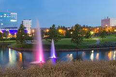 Evening Fountains in Donetsk park. Fountains with purple and lilac backlight in park near Donbass Arena Stadium in Donetsk, Ukraine. Clear blue sky. Evening time royalty free stock photos