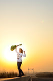 In the evening, girl with a guitar on the road Stock Images