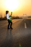 In the evening, girl playing guitar on the road Royalty Free Stock Image