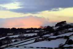 Evening glow over winter snow. Late evening, winter, and an unusual sunset glow is cast over a distant snow-covered hillside Stock Photo