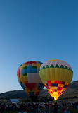 Evening Glow Portrait. Two hot air balloons side by side. One glowing in dusk light Royalty Free Stock Image