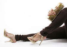 Evening gold shoes and purse. Evening gold shoes on legs and purse on a white background royalty free stock photography