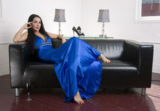 Woman Relaxes Evening Gown Black leather Sofa Royalty Free Stock Image