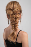 Evening hairstyle. highly collected hair in a braid on blonde girl. Evening hairstyle. Highly collected hair in a braid on blonde girl on black dress on light Stock Photo