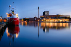 Evening in the harbor, Aarhus Denmark. A clear and blue evening where a coaster and the new Dokk1 building glimmers in the calm and quiet water of the inner Royalty Free Stock Image