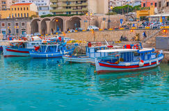 Evening in harbor. HERAKLION, GREECE - OCTOBER 16, 2013: The evening port is the crowded place, full of tourists and fishermen, on October 16 in Heraklion Stock Image