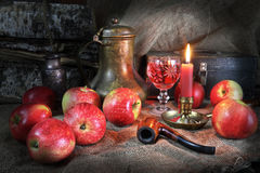 Evening after harvesting of apples with a glass of wine. Still life with apples, an ancient jug, a candle, a tube for smoking and a glass of wine Stock Photos