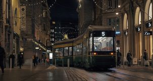 Evening Helsinki and tramway moving in the street, Finland. HELSINKI, FINLAND - JANUARY 07, 2017: Evening city view. Tram moving along the street and turning the stock video