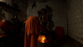 Evening Hindu ceremony automatic Aarti machine plays monk in orange clothes rings in bell and lights lamp with big wick statue of