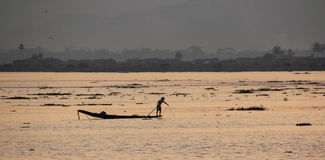 Evening at Inle lake. The sun is setting over lake Inle, and reflects golden in the water. The fisherman standing on their boats, stand as silhuettes against the Royalty Free Stock Images