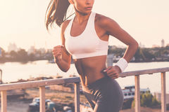 Evening jog. Close-up of beautiful young woman in sports clothing running along the bridge and looking over shoulder Stock Photo