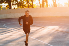 Evening jog of professional athlete, sunset light. Young sprinter training on open-air stadium, free space for text. Backdrop for motivational poster, success Royalty Free Stock Images
