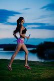 Evening jogging. Young attractive brunette on jogging in evening. Blur motion stock photography